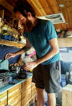John Serbell fixes a meal in the van he and Jayme Serbell transformed into a home.