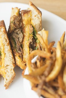 Pangea's terrific duck grilled cheese is topped with arugula and tomato jam and served with seasoned fries.