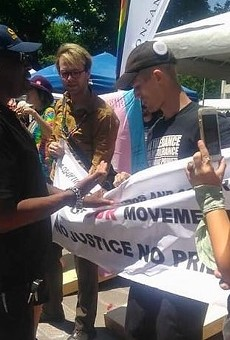 Justin Michalik, center right, holds a protest banner at the Monsanto booth shortly before his arrest on June 26.
