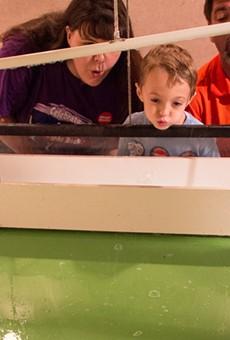 A family enjoys an interactive exhibit at the Magic House.