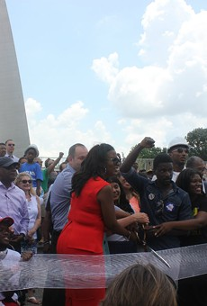 A diverse crowd cuts the ribbon on the Arch renovations