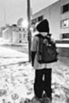 Before the sun rises, Jerad stands outside New Life's      shelter on Locust, waiting for the taxi that takes him to      school.
