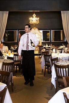 Server David Stiffelman minds the chic dining room at Chez Leon's new location in Clayton.
