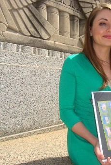 """Vara Lyons, in front of the Mel Carnahan Courthouse in downtown St. Louis, holding a mini-print of a canvas piece titled """"It's Just Paper,"""" by Renee Farmer, a longtime victim's advocate who later became a victim herself."""