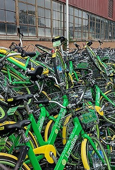Dozens of Lime damaged bikes awaiting repair turned up in an alley behind a warehouse in August.