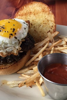 The Farmhouse Burger — two smashed patties, topped with bacon and a peppery eggs.