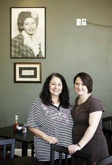 Mary Samuelson (left) and daughter Amy Keller (right) stand beneath a portrait of the restaurant's namesake.