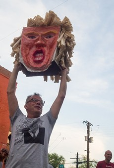 "Francis ""Rich"" Rodriguez, owner of Yaquis on Cherokee, holds El Trumpo's severed head aloft."
