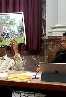During Thursday's committee hearing, 4th Ward Aldermen Sam Moore, left, brought pictures of crumbling north city houses.