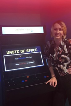 Webster U. graduate Tamsen Reed, next to a game she co-produced for the St. Louis Science Center.