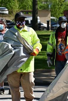 City workers with trash bags head into one of the tent cities on Friday.