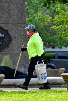 A worker picks up trash after the city removed two tent camps from downtown parks.