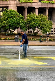 A city worker power washes the LYDA RESIGN painted sign from Tucker Boulevard.