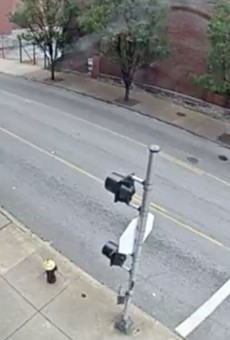 A screen shot shows the suspect in black and a red minivan next to the woman, who is blurred out.