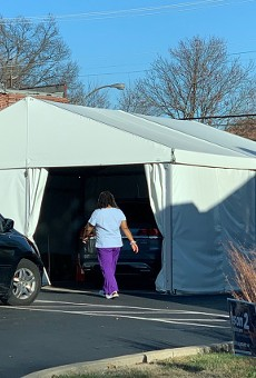 A health-care worker enters a COVID-19 testing tent.