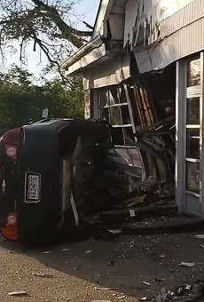 The aftermath of a fatal car accident in which a Chevy Malibu went airborne into a mechanic shop.