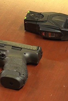 A comparison between the St. Ann police-issue Taser and sidearm  — both colored black.