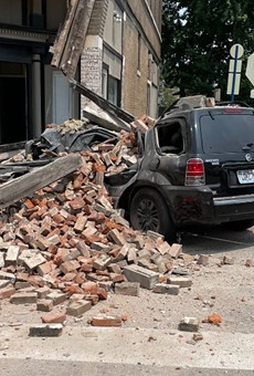 The SUV was mashed below a pile of bricks that fell off the building.