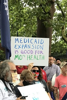 Demonstrators stand outside of the Governor's Mansion in Jefferson City on July 1, 2021 and hold signs urging Gov. Mike Parson to fund voter-approved Medicaid expansion.