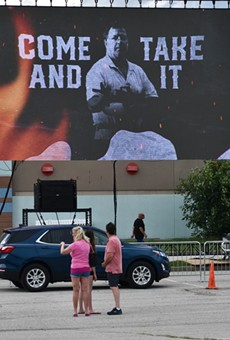 A video banner at a June 28, 2021 rally for U.S. Senate candidate Mark McCloskey.