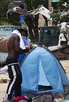 An unhoused resident of Interco Plaza gathers the contents of his tent as city workers clear the encampment.