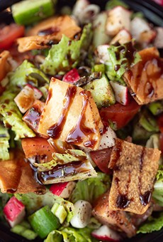 Fattoush salad with romaine, tomatoes, cucumbers and green onions, topped with pita chips, olive oil lemon dressing and pomegranate molasses.