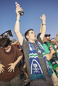 St. Louis soccer fans celebrate Saint Louis FC. The team's fan club supports Props 1 and 2, but the author — a big soccer fan — does not.