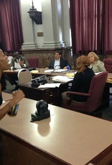 A young woman tells elected officials to find the money for police body cameras.