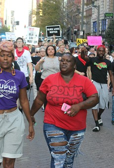 Melissa McKinnies (left) and Ebony Williams lead protesters along Washington Avenue.