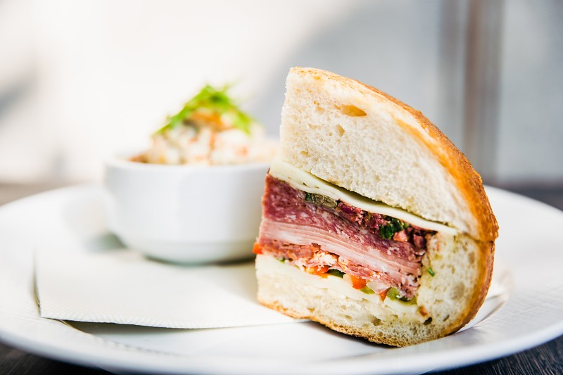 Volpi muffuletta with Genoa salami, capicola, mortadella, provolone, olive tapenade and house-made giardiniera in a sourdough round - COURTESY OF 1764 PUBLIC HOUSE
