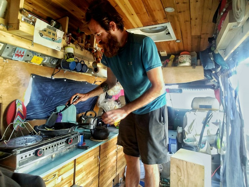 John Serbell fixes a meal in the van he and Jayme Serbell transformed into a home. - COURTESY OF JOHN AND JAYME SERBELL