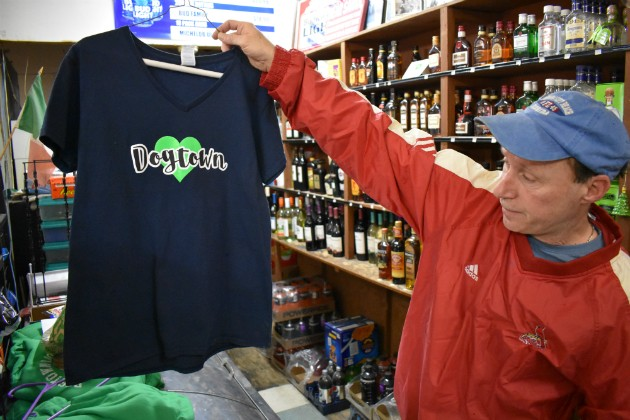 Patrick Wrzesinski, owner of Patrick's Dogtown Liquors, holds up a bullet-pierced T-shirt from a burglary. - PHOTO BY DOYLEMURPHY
