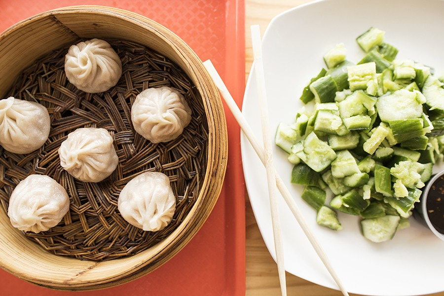Pork soup dumplings are paired here with a side of cucumber with garlic sauce. - MABEL SUEN