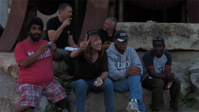 Stephanie, a volunteer, sits with residents of Tent City. In the film, Stephanie ponders at what point is being too involved no longer healthy. - SCREEN SHOT FROM LIVING IN TENTS