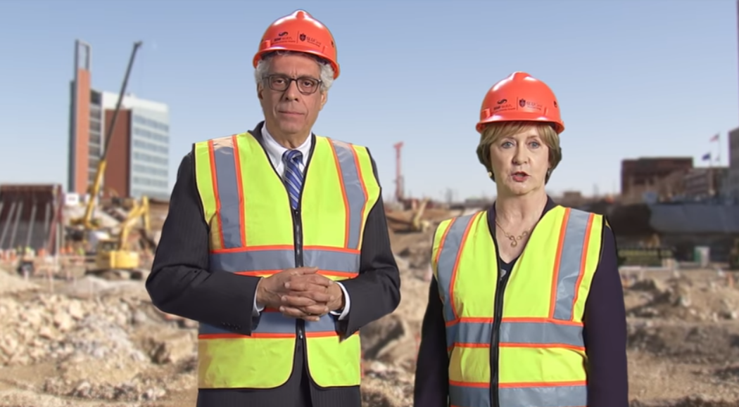 Saint Louis University President Fred Pestello and SSM Health Region President Candace Jennings doing their best to look like they're not standing in front of a green screen. - SCREENSHOT FROM THE VIDEO BELOW