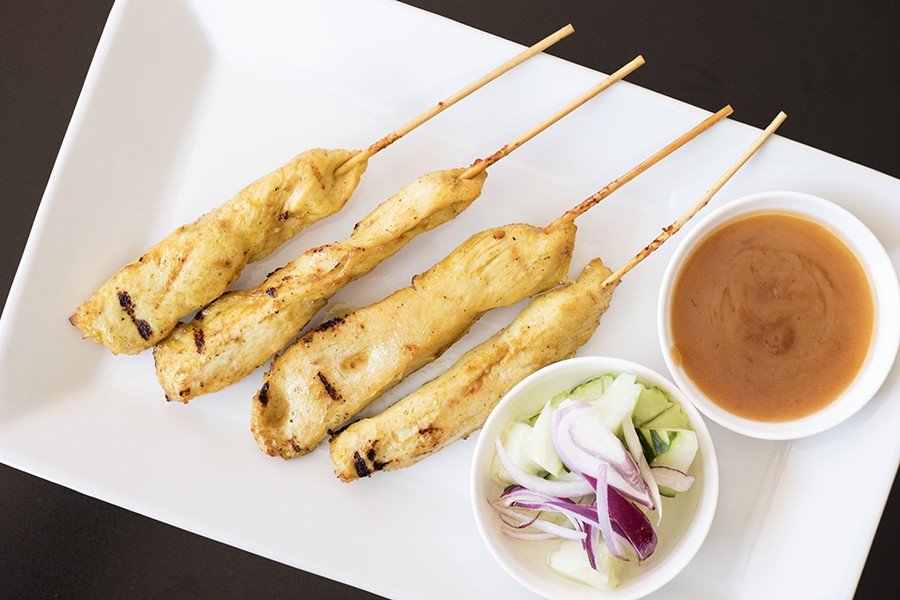 Chicken satay is served with peanut sauce and cucumber salad. - MABEL SUEN