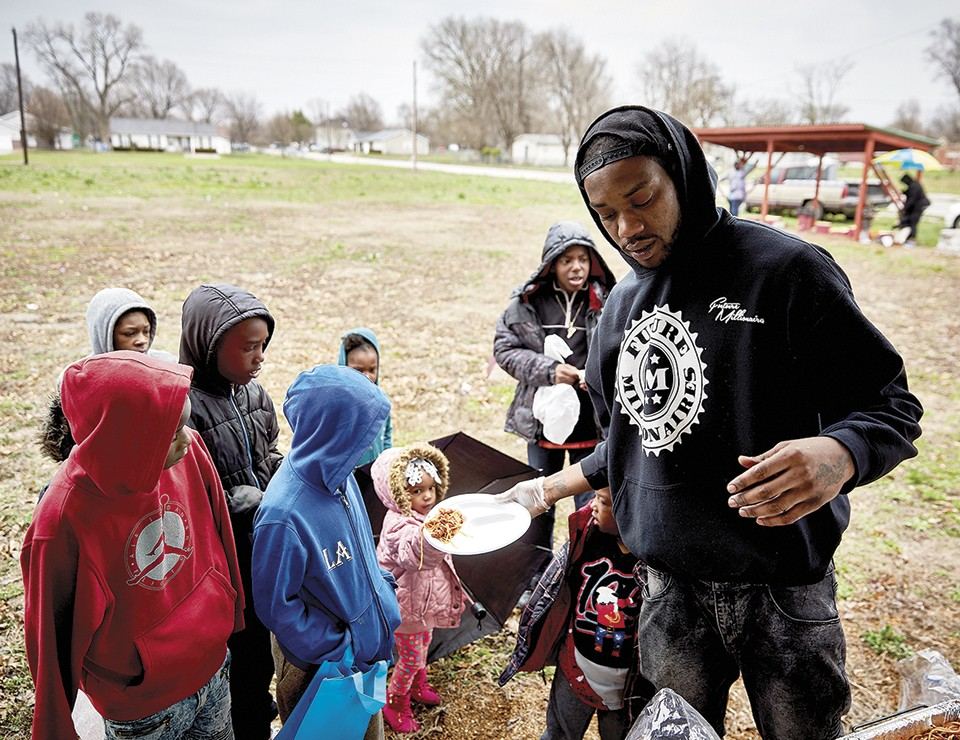 """Liddell serves lunch to children at an Easter event. """"He is at his best when engaging with young people,"""" says SLU's Oberle. - THEO WELLING"""