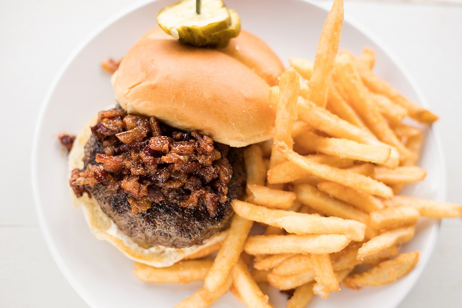 The house burger is topped with beer cheese and bacon onion jam and served with fries. - MABEL SUEN