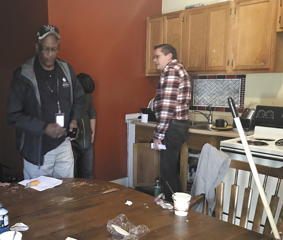 Nathan Cooper, right, tells an inspector he's not to blame for the home's condition. - CAITLIN LEE