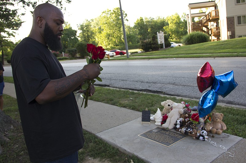 Michael Brown Sr. prepares to lay down a bouquet of roses at a memorial plaque for his son. - DANNY WICENTOWSKI
