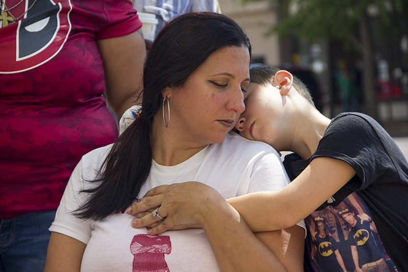 Gina Torres, center, is comforted by one of her remaining sons. - DANNY WICENTOWSKI