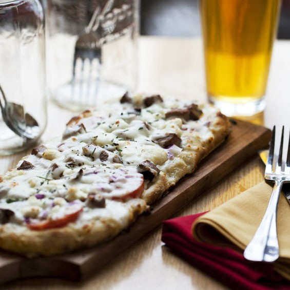 The Steakhouse is parmesan cream, smoky beef brisket, red onion, roma tomato, gorgonzola, rosemary & mozzarella.