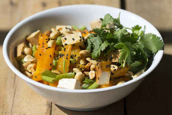 "Lulu's ""Buddha Bowl"" brims with udon noodles, organic tofu, stir-fried vegetables, green onion, cilantro, crushed peanuts, black sesame seeds and homemade peanut sauce."