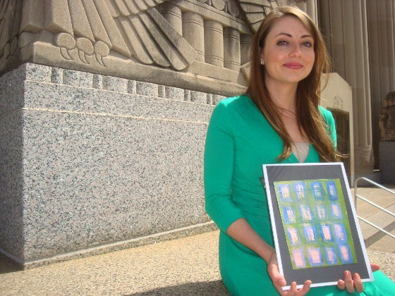"Vara Lyons, in front of the Mel Carnahan Courthouse in downtown St. Louis, holding a mini-print of a canvas piece titled ""It's Just Paper,"" by Renee Farmer, a longtime victim's advocate who later became a victim herself."