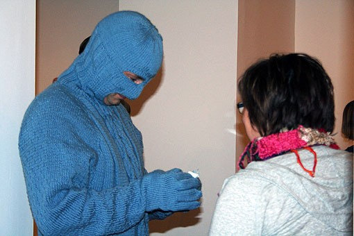 A woman comes up to Sweaterman to receive her coupon of protection for the night. - PHOTO: EMILY GOOD