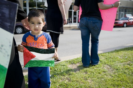 Anis Ghannam, 2, holds a Palestinian flag during the protest.