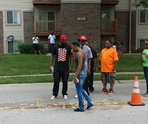 Michael Brown Sr., far left, visits the spot where his son died. - JESSICA LUSSENHOP