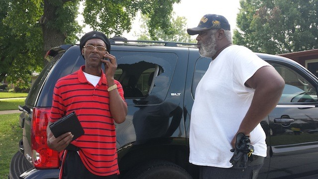 Donald Harry (right) inspects his truck window that was shot out Monday night in Ferguson. - PHOTO BY JESSICA LUSSENHOP