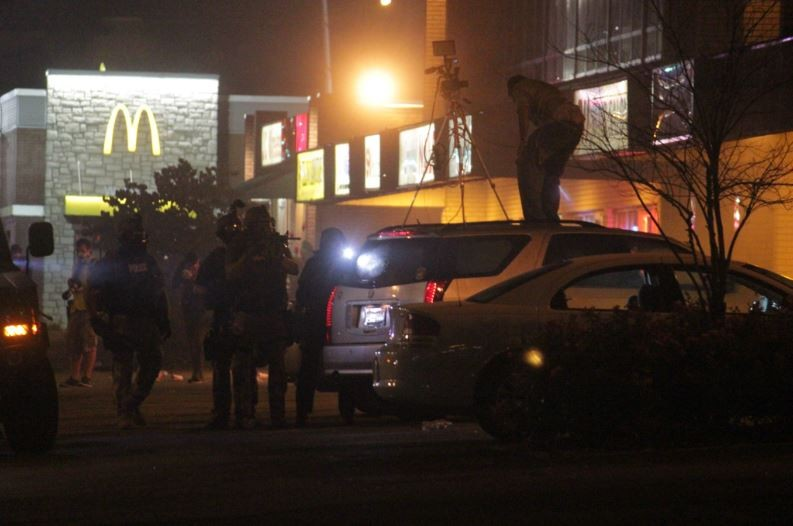 A reporter for KARG Argus Radio films from on top of a car in Ferguson. - DANNY WICENTOWSKI