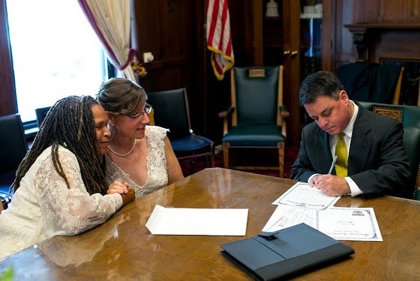 Miranda Duschack and Mimo Davis complete the paperwork portion of their marriage ceremony. - COURTESY MAYOR SLAY'S OFFICE